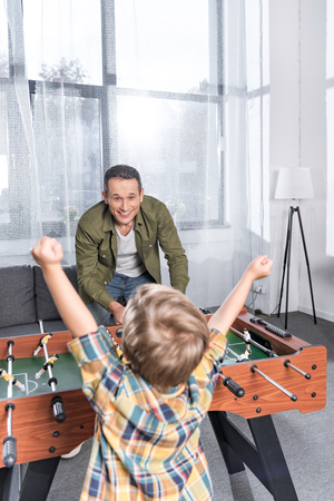 Foto de happy father and son playing table football together at home - Imagen libre de derechos