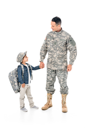 Foto de little boy and father in military uniform holding hands together isolated on white - Imagen libre de derechos