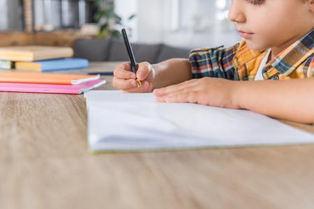 Foto de close-up shot of little schoolboy doing homework - Imagen libre de derechos