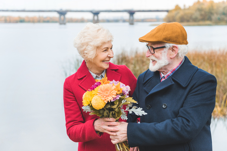 Photo for happy senior couple with bouquet of flowers standing at autumn lake - Royalty Free Image