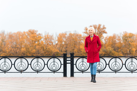 Photo for happy senior woman in red coat on quay with copy space - Royalty Free Image