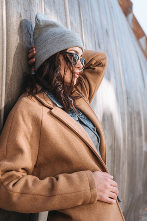 Photo pour Side view of stylish woman in autumn outfit and black sunglasses standing outside - image libre de droit
