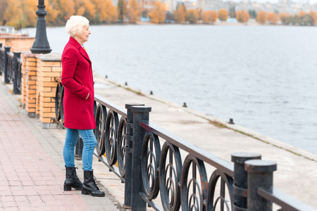 Photo for senior woman in red coat standing on quay - Royalty Free Image