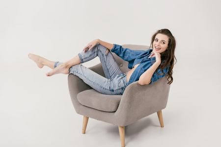 Photo for beautiful sexy woman in denim clothes smiling and looking away while sitting on armchair isolated on grey - Royalty Free Image