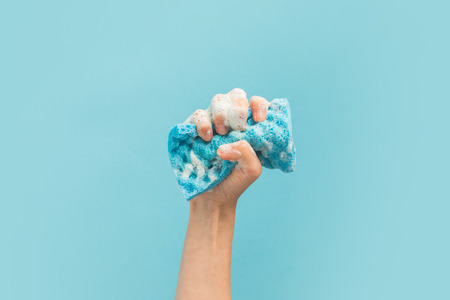 Photo pour cropped view of hand holding washing sponge with foam, isolated on blue - image libre de droit