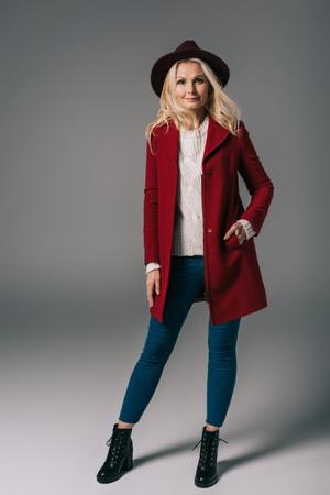 Foto de attractive mature woman in red coat and hat on grey - Imagen libre de derechos