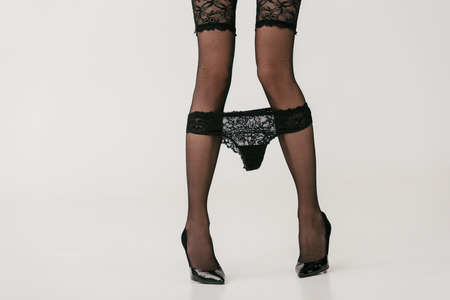 Photo for cropped shot of girl in black stockings taking off lace panties isolated on grey - Royalty Free Image