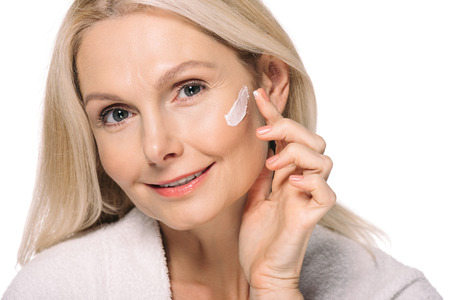 Photo pour smiling mature woman applying cosmetic cream isolated on white - image libre de droit