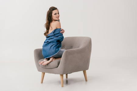 Photo for beautiful young woman in denim shirt sitting with naked shoulders and looking at camera isolated on grey  - Royalty Free Image