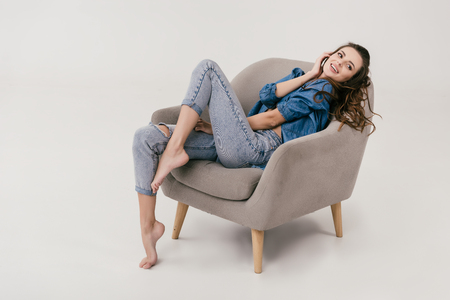 Foto de beautiful smiling sexy woman in denim clothes sitting on armchair and looking away isolated on grey - Imagen libre de derechos