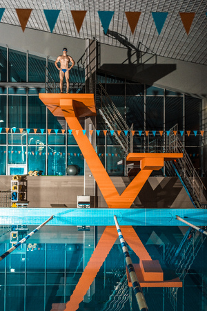 Photo for swimmer standing on diving platform ready to jump at swimming pool - Royalty Free Image
