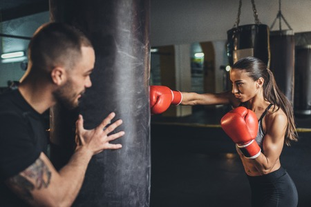 Photo pour handsome young trainer holding punching bag while female boxer training  - image libre de droit