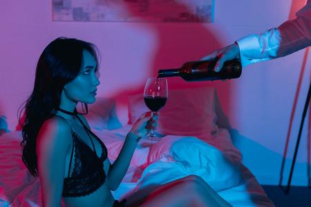 Photo pour man pouring wine for beautiful girlfriend in dark bedroom - image libre de droit