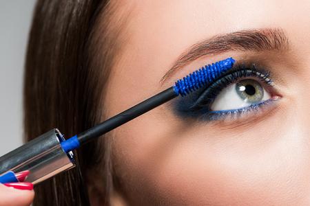 Foto de cropped shot of young woman doing eyelashes makeup with blue brush - Imagen libre de derechos