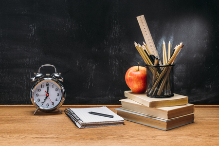 Photo for close up view of fresh apple, clock, notebook, pencils and books on wooden tabletop with empty blackboard behind - Royalty Free Image