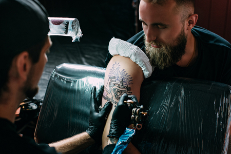 Photo pour selective focus of tattoo artist in gloves with tattoo machine working on tattoo on shoulder in salon - image libre de droit