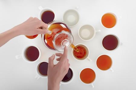 Foto de partial view of person pouring herbal tea in cups on grey - Imagen libre de derechos
