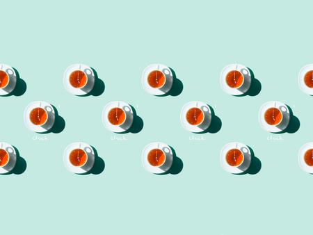 Foto de top view of tea time pattern with white tea cups and saucers on blue - Imagen libre de derechos
