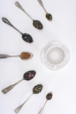 Foto de top view of assorted herbal tea in spoons and empty cup on grey - Imagen libre de derechos
