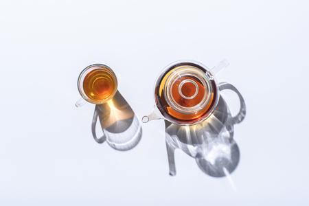 Foto de top view of herbal tea in glass cup and kettle with shadows on grey - Imagen libre de derechos