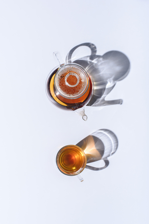 Foto de top view of healing herbal organic tea in glass cup and kettle with shadows on grey - Imagen libre de derechos