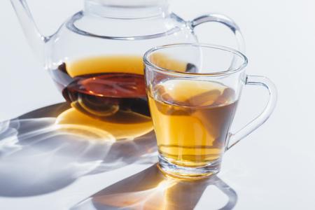 Foto de close-up view of healthy herbal tea in glass cup and kettle on grey - Imagen libre de derechos