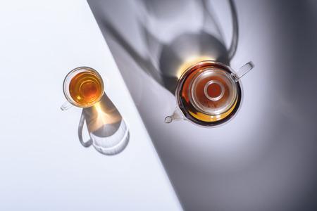 Foto de top view of healthy herbal tea in glass cup and kettle with shadows on grey - Imagen libre de derechos