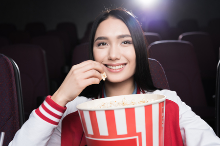 Photo pour young asian girl eating popcorn and watching movie in cinema - image libre de droit