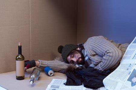 Foto de homeless man sleeping on newspapers in cardboard box - Imagen libre de derechos