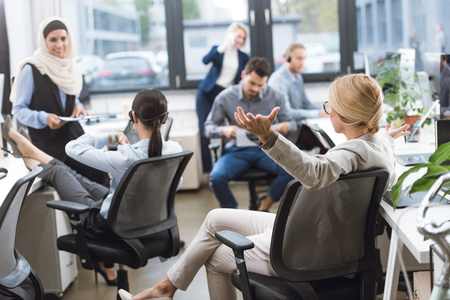 Foto de selective focus of businesswoman with outstretched arms looking at colleagues resting during work in office - Imagen libre de derechos