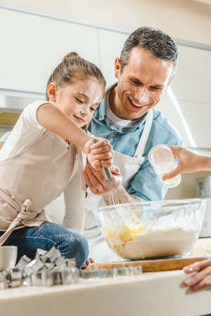 Foto de happy family, little kid with father mixing dough in bowl by hands at kitchen - Imagen libre de derechos
