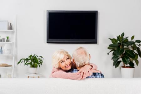 Photo pour senior couple embracing on couch in front of tv - image libre de droit
