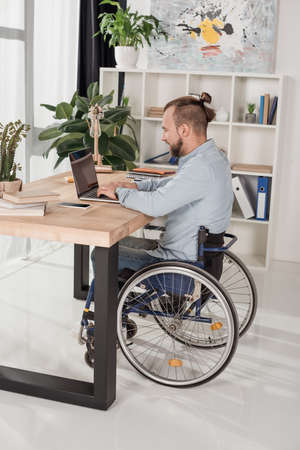 Photo for disabled man on wheelchair using laptop at office - Royalty Free Image
