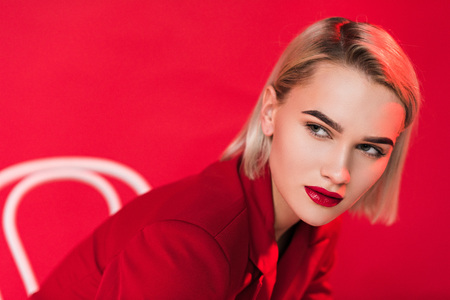 Photo pour portrait of blonde stylish elegant girl posing in red jacket, isolated on red - image libre de droit