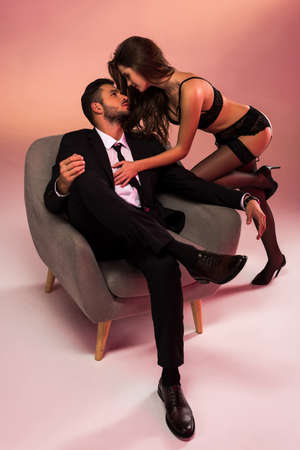 Photo pour successful businessman sitting on armchair with sexy girl in lingerie - image libre de droit