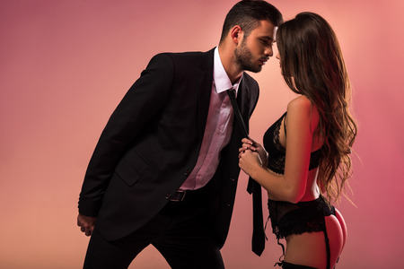 Photo for beautiful girl in lingerie holding necktie of businessman - Royalty Free Image
