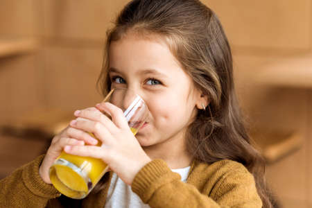 Photo pour adorable kid drinking orange juice in cafe and looking at camera - image libre de droit