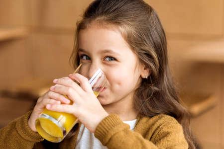 Foto de adorable kid drinking orange juice in cafe and looking at camera - Imagen libre de derechos