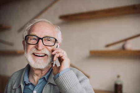 Photo pour happy bearded senior man talking by phone - image libre de droit