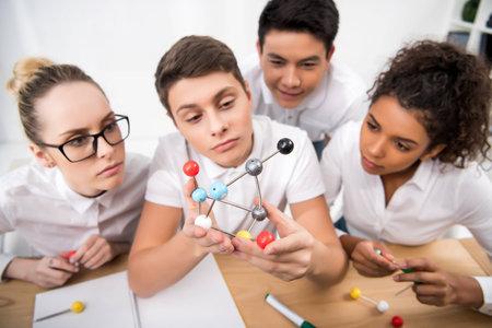 Photo pour young students picking molecular model for chemistry lesson - image libre de droit
