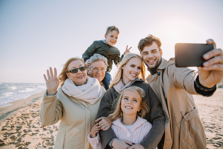 Foto de multigenerational family taking selfie on smartphone at seaside - Imagen libre de derechos