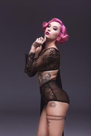 Foto de beautiful pin up girl in transparent lingerie infront of grey background - Imagen libre de derechos