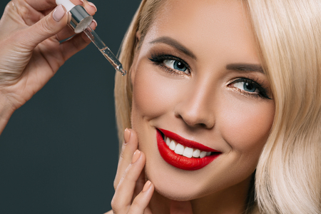 Photo pour gorgeous blonde woman applying serum on her face, isolated on grey - image libre de droit