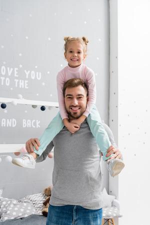 Photo pour happy little daughter riding on father shoulders - image libre de droit