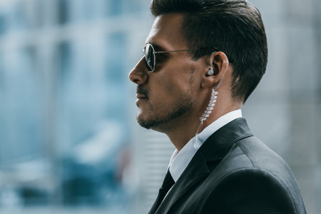 Photo pour profile of handsome security guard with sunglasses and security earpiece - image libre de droit