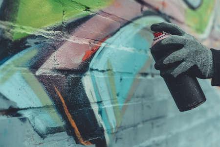 Foto de cropped view of man painting colorful graffiti on wall - Imagen libre de derechos