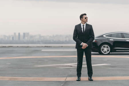 Foto de serious bodyguard standing with sunglasses and security earpiece on helipad and looking away - Imagen libre de derechos