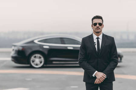 Photo pour serious bodyguard standing with sunglasses and security earpiece on helipad - image libre de droit