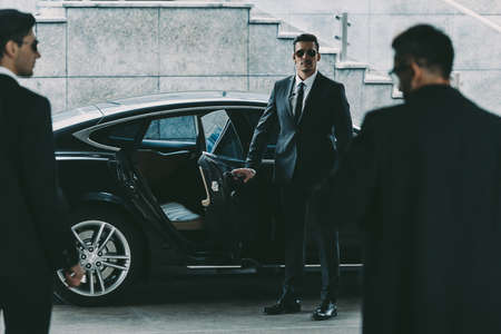 Foto de bodyguard in sunglasses opening car door to businessman - Imagen libre de derechos