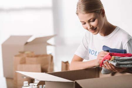 Foto de beautiful female volunteer putting clothes into box for charity - Imagen libre de derechos